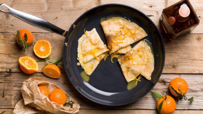 Poêle avec des crèpes et oranges